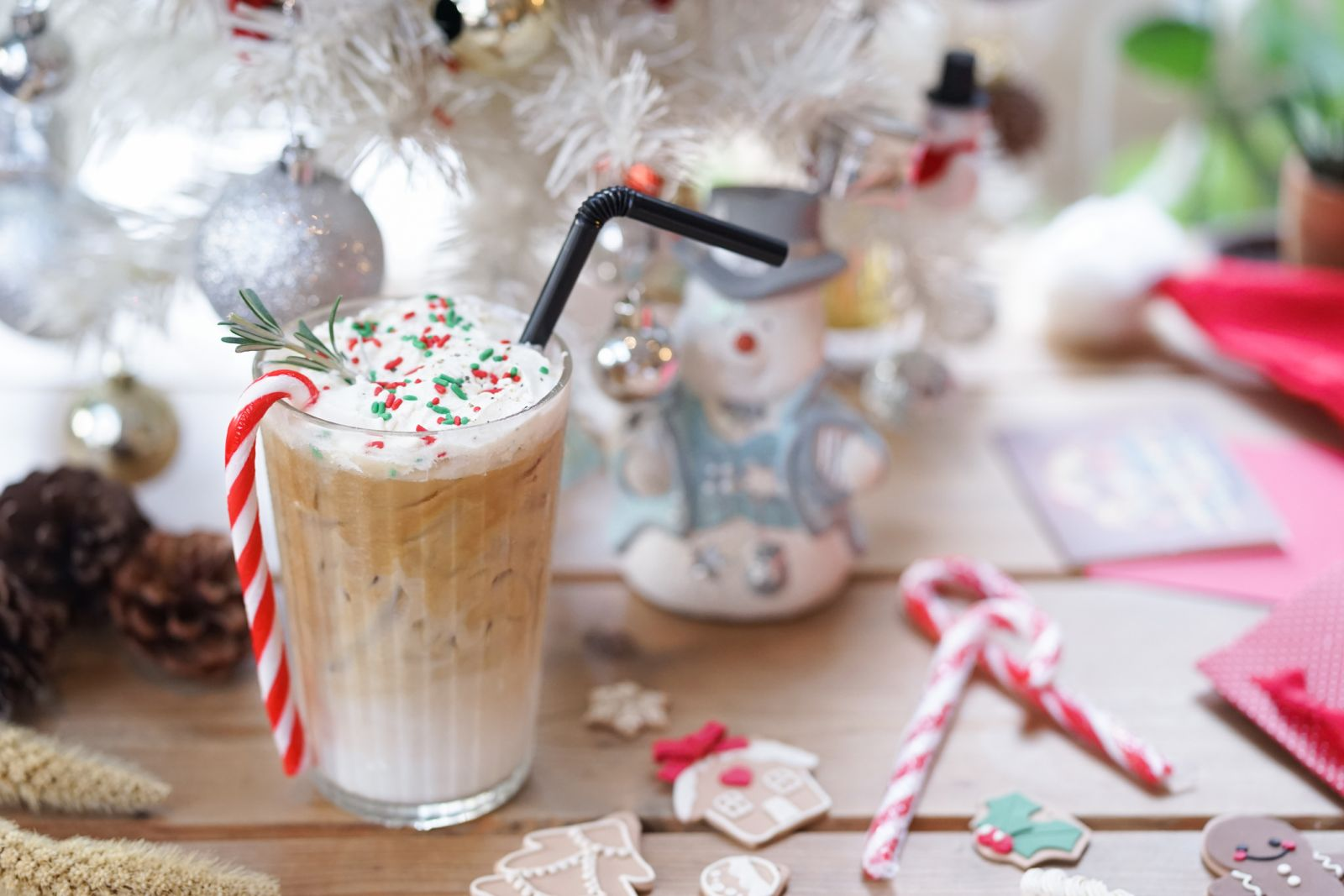 Holiday themed Iced coffee in front of a white Christmas tree